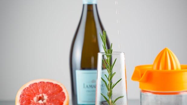 Grapefruit juice pouring into flute for grapefruit prosecco cocktail