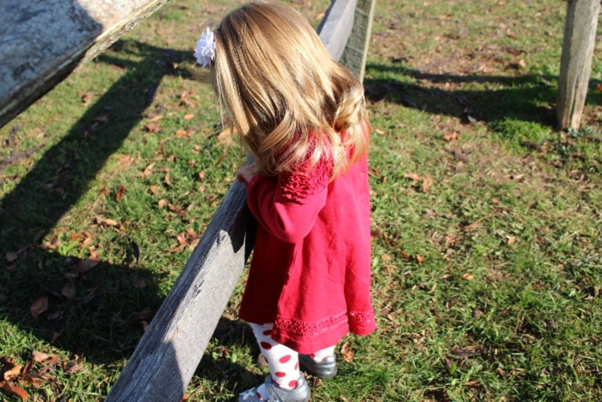baby red dress with tights showing on fence