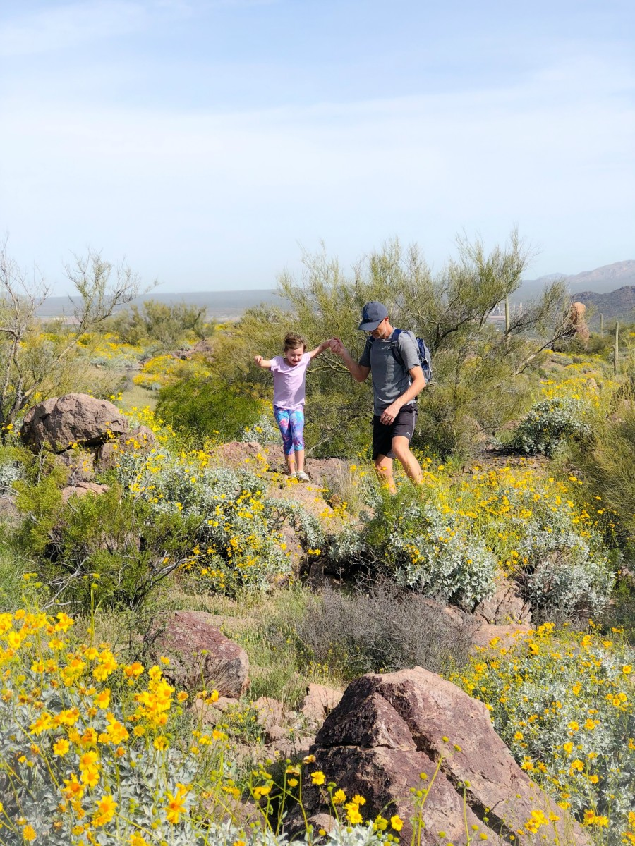father helping daughter on hike