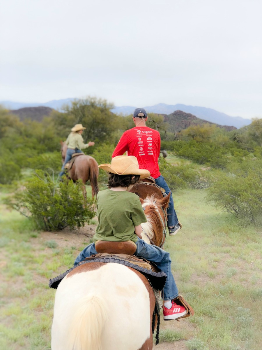 child horseback riding in the desert