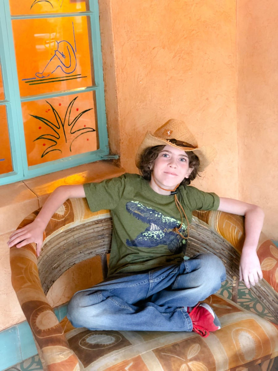 kid in a cowboy hat sitting on a chair
