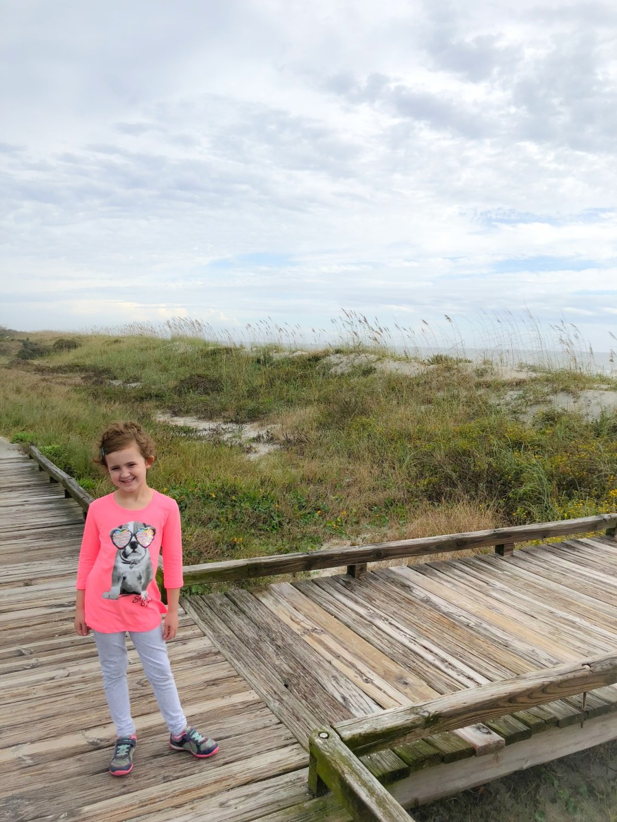 little girl standing on the boardwalk on the beach