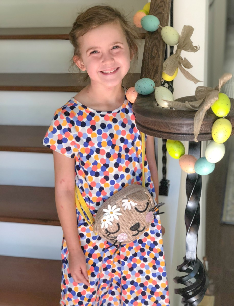 little girl standing on stairs next to banister decorated for Easter